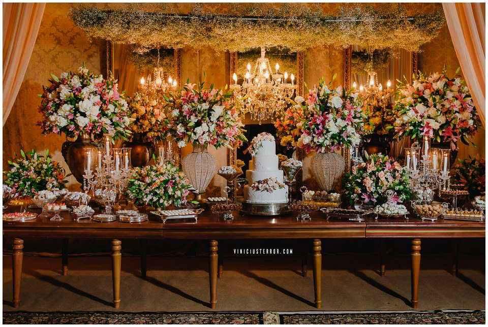 mesa-de-bolo-classica-com-arranjos-de-flores-suspensos-para-casamento-noturno