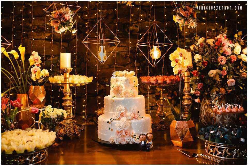 mesa-de-bolo-com-velas-e-arranjos-florais